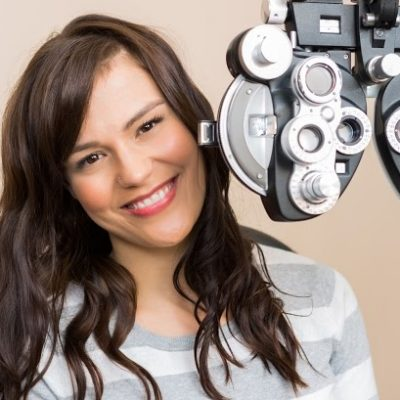 Portrait of beautiful young woman sitting behind phoropter during eye exam
